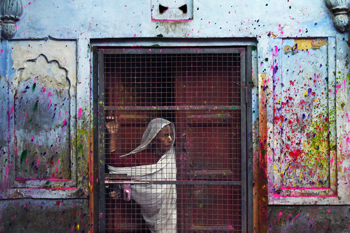 "An Indian widow watches as others dance as they celebrate Holi or ""festival of colors"" in Vrindavan on Tuesday. Widows congregated on a small patio of the ashram in which they live and danced and played with colored powder to celebrate the occasion. The widows of this and other ashrams in this northern town are sponsored by the NGO Sulabh International, which funds most of their needs.  Shunned from society when their husbands die, not for religious reasons, but because of tradition, many Indian widows have been otracized from society and no longer live with their families and are forced to beg for food. Almost 2,000 of the estimated 34 million widows currently living in India live in Vrindavan and benefit from the welfare extended by the NGO. (ROBERTO SCHMIDT/AFP/Getty Images)"