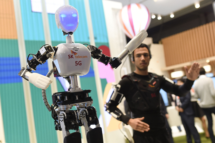 A man operates an SK telecom robot during the 2015 Mobile World Congress in Barcelona on March 3, 2015. Phone makers will seek to seduce new buyers with even smarter Internet-connected watches and other wireless gadgets as they wrestle for dominance at the world's biggest mobile fair. (JOSEP LAGO/AFP/Getty Images)