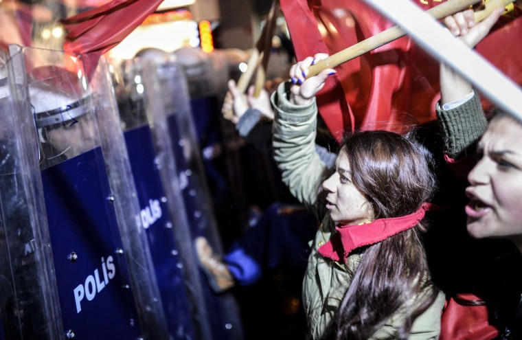 Turkish women beat riot police shields on March 8, 2015 as they try to cross a police cordon to reach Taksim square during a rally on Istiklal avenue in Istanbul to mark International Women's Day. (Bulent Kilic/AFP/Getty Images)