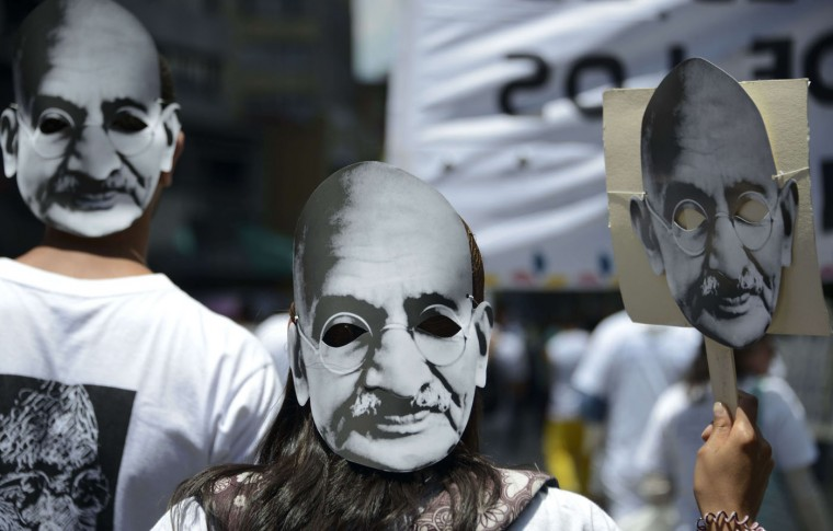 "People wear masks with the image of Indian independence leader Mahatma Gandhi during the ""March for Life""with a call to defeat hatred and keep society together in peace, in Medellin, Antioquia department Colombia, on International Women's Day on March 8, 2015. (Raul Arboleda/AFP/Getty Images)"