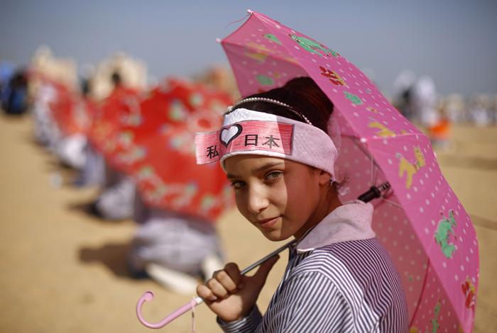 A Palestinian school girl wearing a banner on her forehead bearing Japanese writing gathers with fellow classmates in solidarity with Japan, near the Japanese-funded housing project in Khan Yunis in the southern Gaza Strip on Monday. The event was organized by the United Nations Relief and Works Agency to mark the fourth anniversary of the March 11, 2011, earthquake and tsunami that killed thousands and set off a nuclear crisis in Japan. (MOHAMMED ABED/AFP/Getty Images)