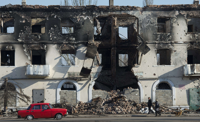 People walk past a building damaged in fighting in Vuhlehirsk, Ukraine, just south of Debaltseve on Monday. The city, captured from Ukrainian troops by soldiers of the self-proclaimed Donetsk People's Republic on Feb. 18, and damaged in the battle, is slowly coming back to life. (JOHN MACDOUGALL/AFP/Getty Images)