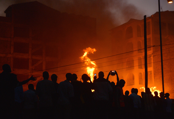 Residents of a Nairobi, Kenya, suburb use their phones to record a blaze at dusk Monday that gutted a residential plot. (TONY KARUMBA/AFP/Getty Images)