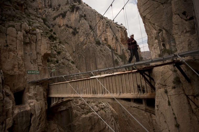 """A man crosses a footbridge during a visit to the foot-path """"El Caminito del Rey"""" (King's little path) a narrow walkway hanging and carved on the steep walls of a defile in Ardales near Malaga on March 15, 2015. (Jorge Guerrero/AFP/Getty Images)"""