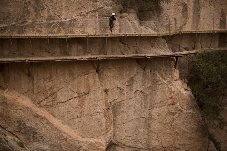 """A person admires the scenery during a visit to the foot-path """"El Caminito del Rey"""" (King's little path) a narrow walkway hanging and carved on the steep walls of a defile in Ardales near Malaga on March 15, 2015. (Jorge Guerrero/AFP/Getty Images)"""