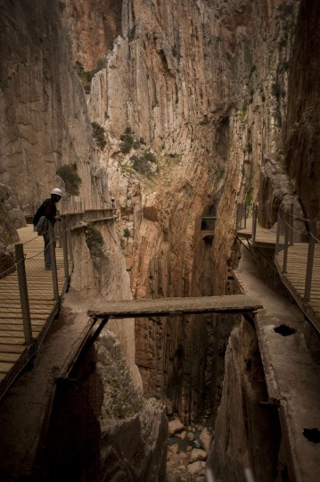 """A journalist admires the scenery during a visit to the foot-path """"El Caminito del Rey"""" (King's little path), a narrow walkway hanging and carved on the steep walls of a defile in Ardales near Malaga on March 15, 2015. (Jorge Guerrero/AFP/Getty Images)"""
