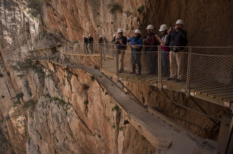 """Journalists and visitors take photographs during a visit to the foot-path """"El Caminito del Rey"""" (King's little path), a narrow walkway hanging and carved on the steep walls of a defile in Ardales near Malaga on March 15, 2015. (Jorge Guerrero/AFP/Getty Images)"""