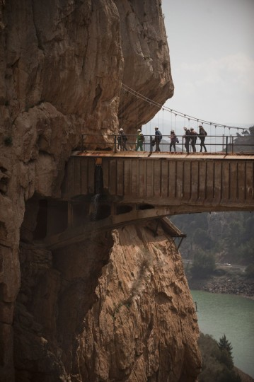 """Journalists and visitors cross a bridge during a visit to the foot-path """"El Caminito del Rey"""" (King's little path) a narrow walkway hanging and carved on the steep walls of a defile in Ardales near Malaga on March 15, 2015. (Jorge Guerrero/AFP/Getty Images)"""