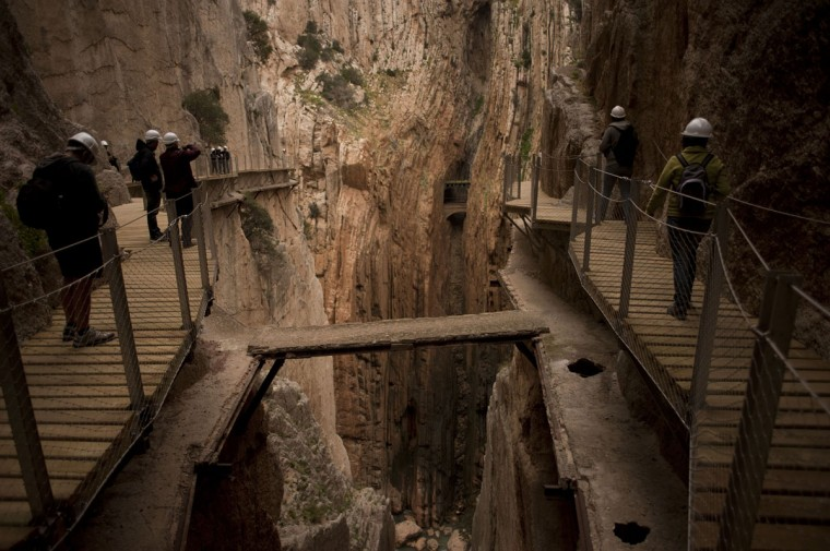 """Journalists and visitors walk during a visit to the foot-path """"El Caminito del Rey"""" (King's little path) a narrow walkway hanging and carved on the steep walls of a defile in Ardales near Malaga on March 15, 2015. (Jorge Guerrero/AFP/Getty Images)"""