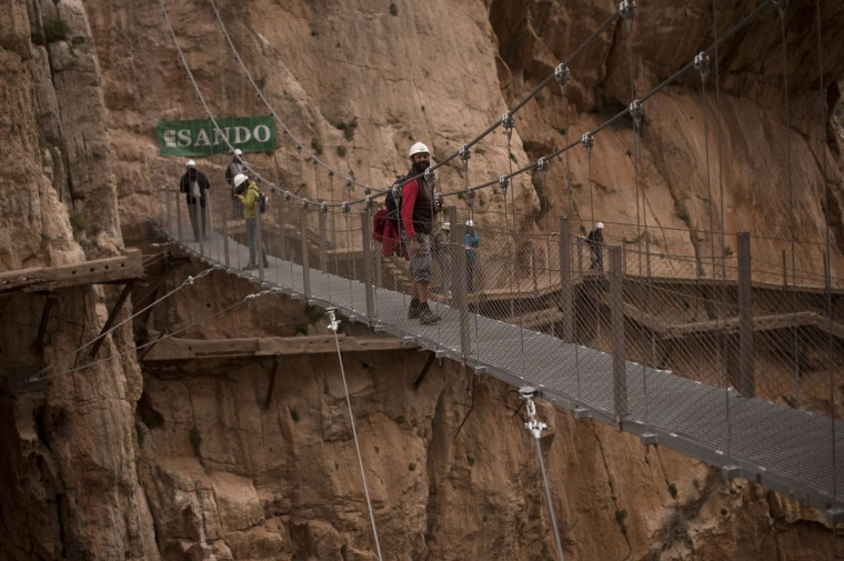 """Journalists walk during a visit to the foot-path """"El Caminito del Rey"""" (King's little path) a narrow walkway hanging and carved on the steep walls of a defile in Ardales near Malaga on March 15, 2015. (Jorge Guerrero/AFP/Getty Images)"""