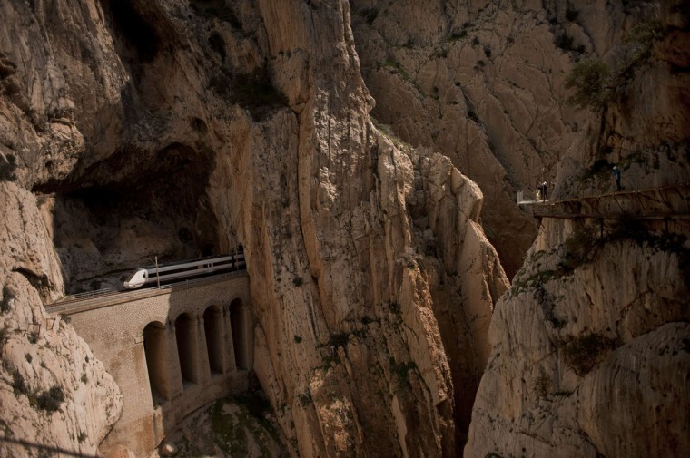 "A train passes through a tunnel in the rocks as people walk the foot-path ""El Caminito del Rey"" (King's little path) a narrow walkway hanging and carved on the steep walls of a defile in Ardales near Malaga on March 15, 2015. The one meter wide and 7.7 km long path, hanging from Ardales' defile at 100 meter high, was closed in the mid 90's after several hikers resulted dead when walking it. Once restored it will be reopened to the public on March 28, 2015. (AFP Photo/Jorge Guerrero )"