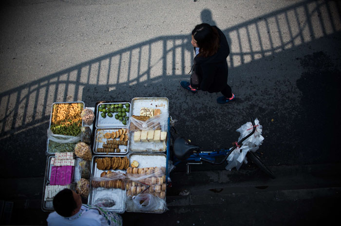 A vendor sells Chinese sweets at a market along a street in Shanghai on Tuesday. (JOHANNES EISELE/AFP/Getty Images)