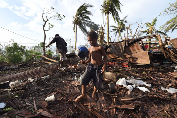 This photo taken on Monday shows a young boy kicking a ball as his father searches through the ruins of their family home in Vanuatu's capital Port Vila after Cyclone Pam ripped through the island nation. (DAVE HUNT/AFP/Getty Images)