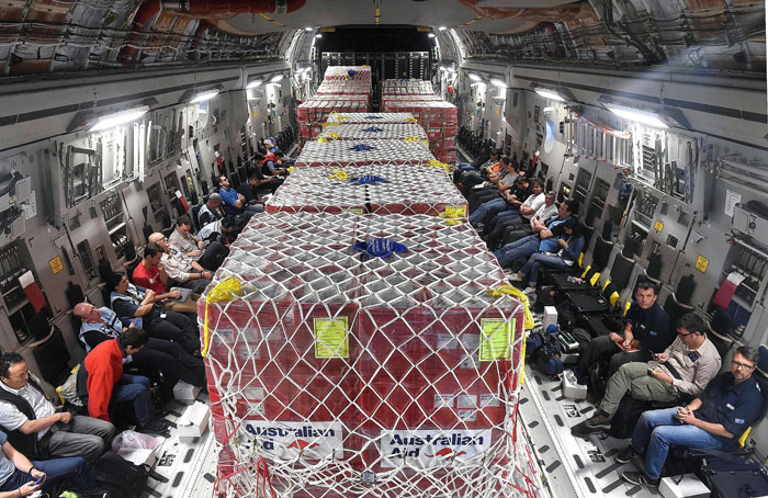 "This photo taken on Monday shows an Australian RAAF C-17 Globemaster plane full of aid on the way to Vanuatu's airport in the capital Port Via after Cyclone Pam ripped through the island nation. The UN said on Tuesday that 24 people had been killed by Cyclone Pam, as the Pacific nation's president pleaded for help to rebuild the archipelago's ""completely destroyed"" infrastructure. (DAVE HUNT/AFP/Getty Images)"