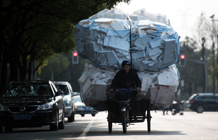 A man rides his tricycle loaded with polystyrene boxes in Shanghai on Tuesday. The world's second-largest economy expanded 7.4 percent last year, the slowest since 1990, as authorities try to transform the growth model to one in which consumer spending takes over as the key engine. (JOHANNES EISELE/AFP/Getty Images)