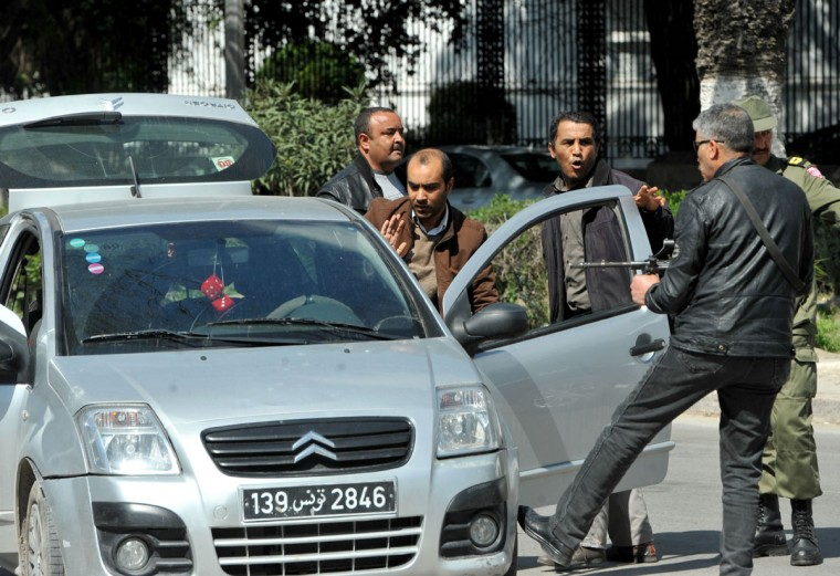 Armed Tunisian policemen in plainclothes stop a vehicle as security forces secure the area after gunmen attacked Tunis' famed Bardo Museum on March 18, 2015. At least seven foreigners and a Tunisian were killed in an attack by two men armed with assault rifles on the museum, the interior ministry said. (AFP Photo/Fethi Belaid)