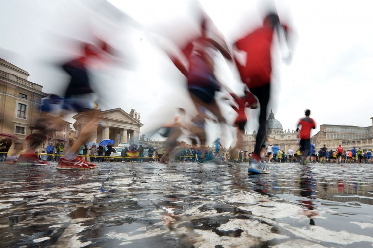 People run in front of St Peter's basilica during the 21th Marathon of Rome on March 22, 2015. (AFP Photo/Tiziana Fabi)