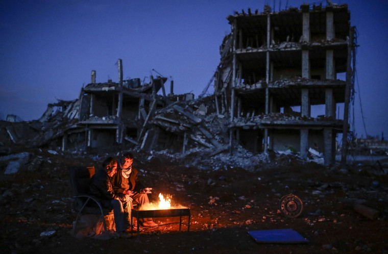 Kurdish men sit near bonfire near a destroyed building, in the Syrian Kurdish town of Kobane, also known as Ain al-Arab, on March 22, 2015. (AFP Photo/Yasin Akgul)