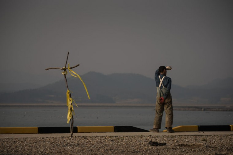 In a photo taken on Friday, a habor worker stands beside a cross adorned with yellow ribbons at Paengmok harbor, near the site of the sunken Sewol ferry, on Jindo island, on the southern tip of the South Korean peninsula. South Korea is preparing to mark the first anniversary of the April 16, 2014, Sewol ferry disaster, which was carrying 476 people when it capsized off the southern island of Jindo. Of the 304 who died, 250 were students from the same high school. The tragedy -- blamed by many on regulatory failings, official incompetence and the ship's illegal redesign -- plunged the nation into a lengthy period of mourning. (ED JONES/AFP/Getty Images)