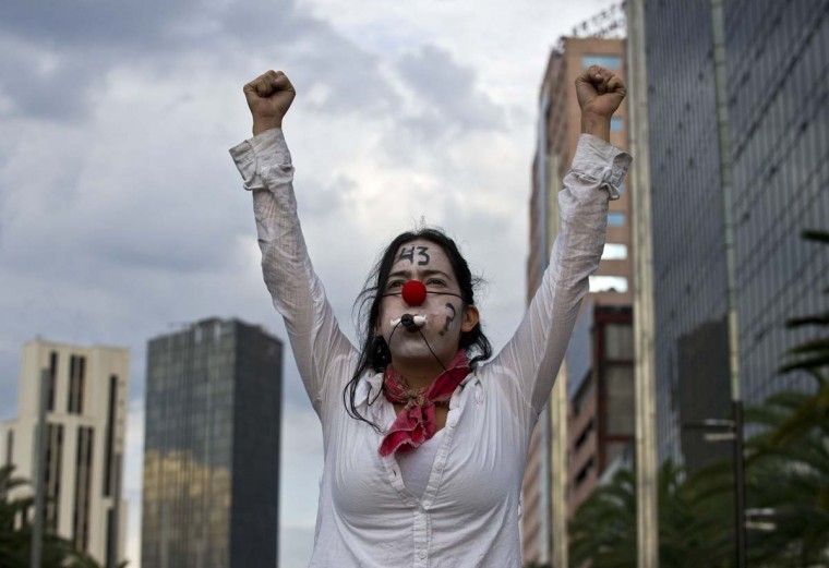 A woman protests in Mexico City on March 26, 2015, during a march to mark six months of the disappearance of 43 students from a rural school in Ayotzinapa.  || CREDIT: RONALDO SCHEMIDT - AFP/GETTY IMAGES