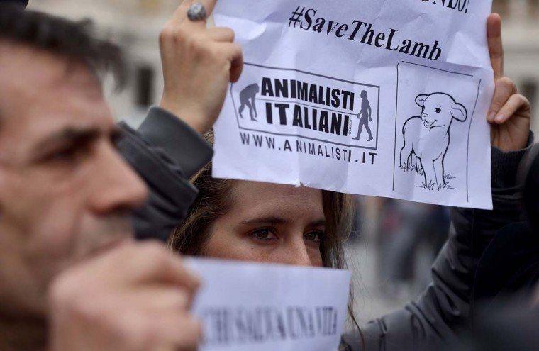 "Activists of the animal rights movement ""Animalisti Italiani"" (Italian Animals) hold placards reading ""Who saves a life saves the world"", during a gathering outside St. Peter basilica on March 27, 2015, asking to ban lamb from the Easter's traditional meal.  