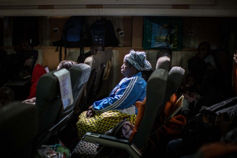 A passenger listens to a preacher delivering a sermon on the fourth class deck aboard of one of the ferries linking the two major hubs of the Kivu region, Goma in the north and Bukavu in the south on March 26, 2015.  || CREDIT: FEDERICO SCOPPA - AFP/GETTY IMAGES