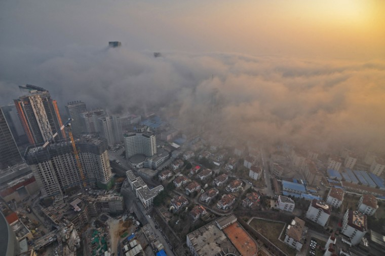 This photo taken on Sunday shows heavy fog covering buildings in Qingdao, east China's Shandong province. Falls in Chinese housing prices decelerated in March from the previous month, a survey showed on Tuesday, after authorities loosened mortgage and tax policies as growth in the world's second-largest economy slows. (AFP PHOTOSTR/AFP/Getty Images)