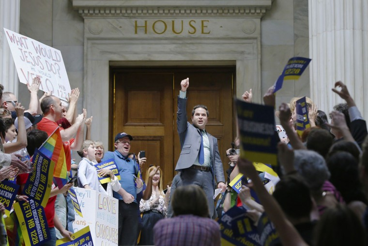 Rep. Warwick Sabin, D-Little Rock, center, cheers with protesters outside of the House chamber at the Arkansas state Capitol in Little Rock, Ark., Monday, March 30, 2015. A House committee earlier Monday advanced an amended version of a bill that opponents say allows discrimination against gays and lesbians. (AP Photo/Danny Johnston)