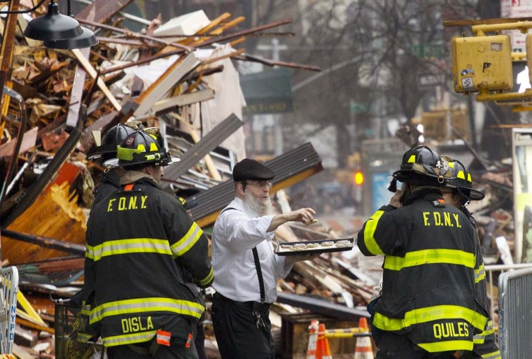A man distributes pastries to weary firefighters at the site of an explosion and fire in the East Village neighborhood of New York, Friday, March 27, 2015. Thursday's inferno caused the collapse of three buildings and fire damage to a fourth, the fire department said. It left four people in critical condition and more than a dozen others injured and at least one family searching for a loved one.  || CREDIT: MARK LENNIHAN - AP PHOTO