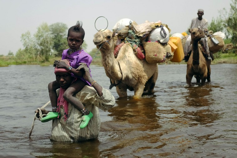 Herdsmen and others cross a tributary of Lake Chad to the village of N'Gouboua, Chad, Thursday, March 5, 2015, using the same route the Nigerian refugees used to flee Boko Haram. Boko Haram militants arrived in N'gouboua before dawn on Feb. 13, marking the first attack of its kind on Chad. By the time the scorched-earth attack ended, they had burned scores of mud-brick houses by torching them with gasoline and had killed at least eight civilians and two security officers. Some 3,400 Nigerian refugees had been living in the village at the time of the attack, and all have since been relocated further inland. (AP Photo/Jerome Delay)