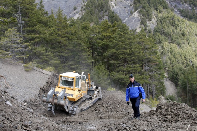 Gendarme Bruno Hermignies stands by a bulldozer clearing a path to the crash site near Seyne-les-Alpes, France, Monday, March 30, 2015. European investigators are focusing on the psychological state of a 27-year-old German co-pilot who prosecutors say deliberately flew a Germanwings plane carrying 150 people into a mountain, a French police official said Monday. (AP Photo/Claude Paris, Pool)