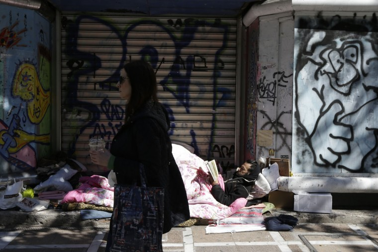 A homeless man reads a book in central Athens, on Monday, March 2, 2015. Germany's finance minister Wolfgang Schaeuble said Sunday that he trusts Greece's current government to fulfill the conditions for the bailout deal, but also made clear the country would not receive any further money if it didn't. (AP Photo/Thanassis Stavrakis)