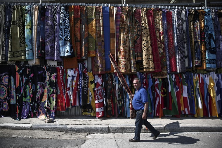 A man makes his way to hang a fabric outside his souvenir shop at Monastiraki tourist district in Athens, on Thursday, March 12, 2015. Talks between Greece and its creditors began in Brussels on Wednesday to cement a series of reforms Athens must implement in order to get the remaining bailout funds released and avoid bankruptcy. (AP Photo/Yorgos Karahalis)