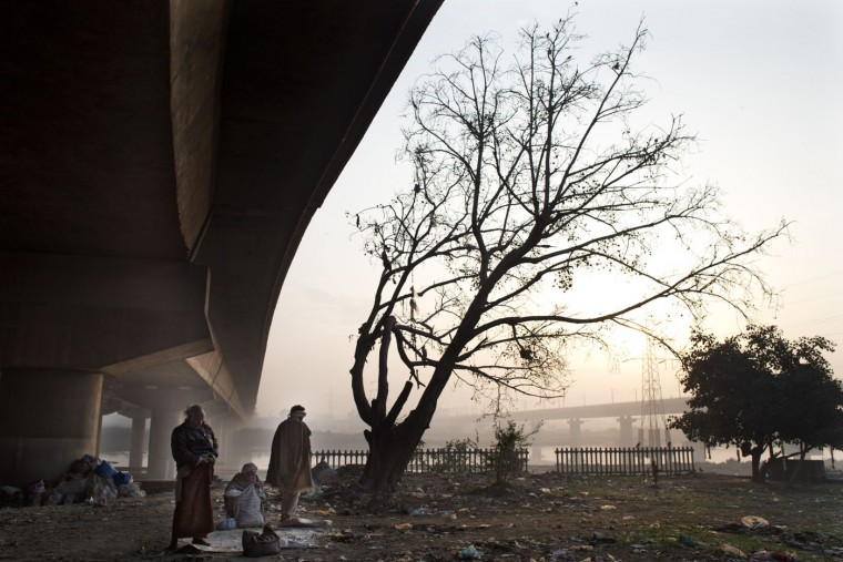 Homeless Indian men prepare themselves for the day ahead as they rise in the early morning near the banks of the River Yamuna, in New Delhi, India, Thursday, March 12, 2015. Some 800 million people in the country live in poverty, many of them migrating to big cities in search of a livelihood and often ending up on the streets. (AP Photo/Bernat Armangue)