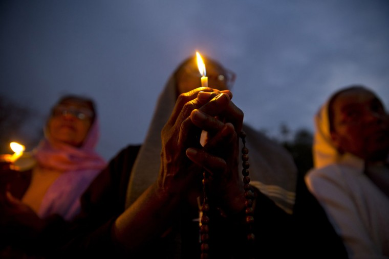 Christian nuns pray as they hold a candle light vigil to condemn the gang rape of a nun at a Christian missionary school in eastern India outside the Sacred Heart cathedral in New Delhi, India, Monday, March 16, 2015. According to police a nun in her 70s was gang-raped by a group of bandits when she tried to prevent them from committing a robbery in the Convent of Jesus and Mary School in West Bengal state's Nadia district. The attack early Saturday is the latest crime to focus attention on the scourge of sexual violence in India. (AP Photo/Saurabh Das)