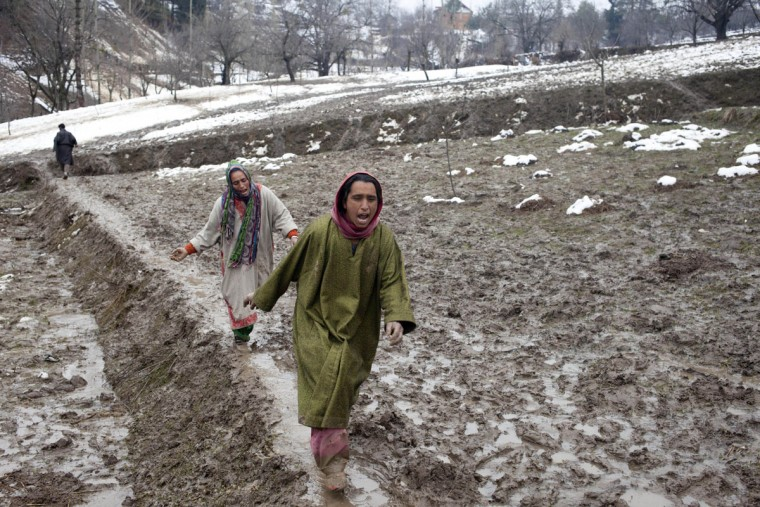 Kashmiri women wail and rush towards the body of a relative, victim of a landslide, as the same is recovered in the village of Laden some 45 Kilometers (28 miles) west of Srinagar, Indian-controlled Kashmir, Monday, March 30, 2015. Hundreds of Kashmiris in both India and Pakistan moved to higher ground Monday as rain-swollen rivers swamped parts of the disputed Himalayan region placed under an emergency flood alert just six months after some 600 people died in flooding that left the region in shambles. (AP Photo/Dar Yasin)
