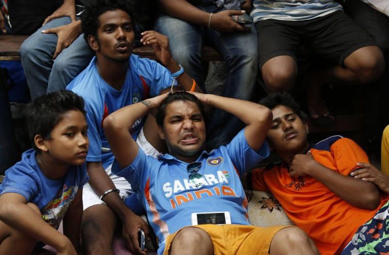 Indian cricket fans react as they watch on television the ICC Cricket World Cup semifinal match between India and Australia in Mumbai, India, Thursday, March 26, 2015. Australia ended 2011 champion India's unbeaten run at the World Cup with a 95-run victory Thursday. (AP Photo/Rajanish Kakade)