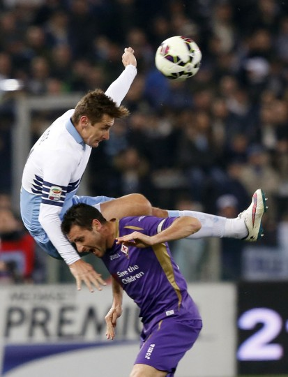 Lazio's Miroslav Klose, left, jumps over Fiorentina's Manuel Pasqual as they vie for the ball during a Serie A soccer match between Lazio and Fiorentina, at Rome's Olympic stadium, Monday, March 9, 2015. (AP Photo/Riccardo De Luca)