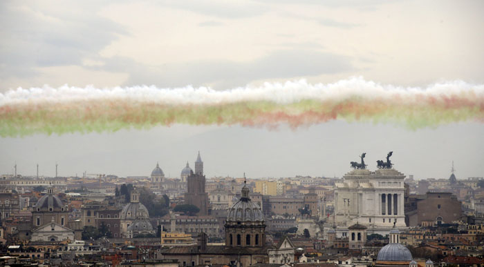 "Smoke trails in the colors of the Italian national flag are released by The ""Frecce Tricolori"" Italian Air Force acrobatic squad as they fly over Rome on Tuesday to mark the 154th anniversary of the Italian Unification. (Gregorio Borgia/AP)"
