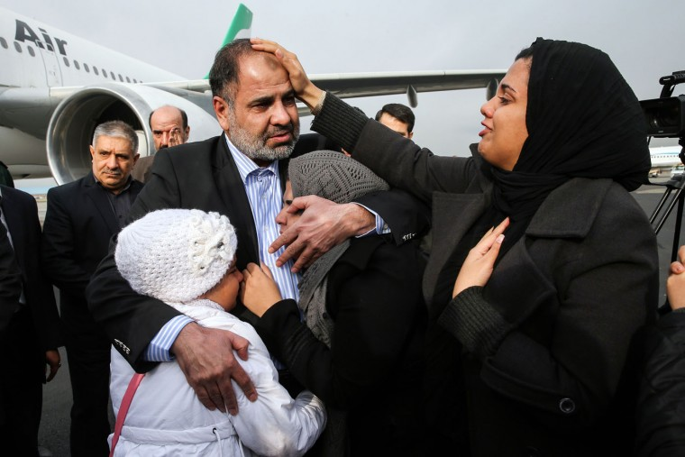 Iranian diplomat Nour Ahmad Nikbakht, abducted in Yemen in 2013, embraces his daughters at Mehrabad airport after being freed and returning home, in Tehran, Iran, Thursday, March 5, 2015. Iran said Thursday that a team of special operatives has freed the Iranian diplomat abducted more than 19 months ago in Yemen, a rare acknowledgment by Tehran of an intel operation carried out on foreign soil. (AP Photo/ISNA, Amir Pourmand)
