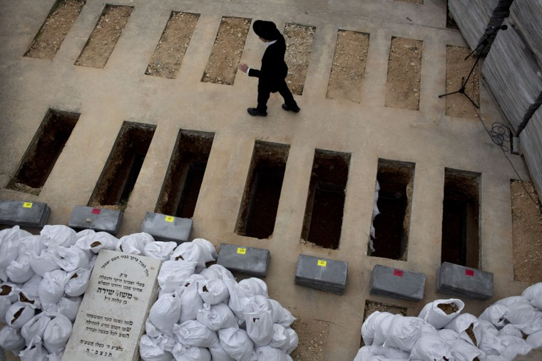 A Jewish boy looks at the graves of seven Jewish siblings killed in a New York house fire, ahead of their burial, in Jerusalem, Monday, March 23, 2015. The bodies of the children, ages 5 to 16, were flown to Israel overnight from New York and were immediately taken to Jerusalem in a convoy escorted by police. According to Jewish tradition, funerals take place as soon as possible after death. (AP Photo/Ariel Schalit)