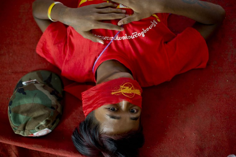 A student protester lies on a monastery floor after police surrounded the monastery apparently to prevent them from proceeding with a protest march to Yangon from Letpadan, north of Yangon, Myanmar, Monday, March 2, 2015. Truckloads of police prevented hundreds of students from marching onward to Myanmar's old capital Monday to protest a new law that they say will curb academic freedom. (AP Photo/Gemunu Amarasinghe)