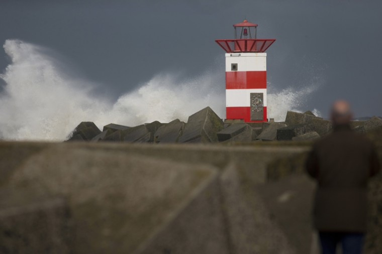 A man watches as the sea batters against a lighthouse during stormy weather at the entrance to the port of Scheveningen, near The Hague, Netherlands, on Tuesday. A storm with wind speeds of up to 68 miles per hour passed over The Netherlands and Germany. (Peter Dejong/AP)