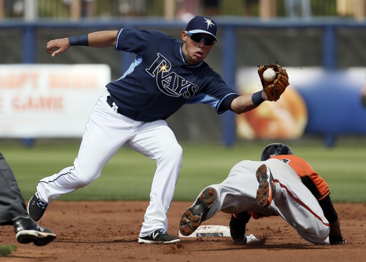 Tampa Bay Rays shortstop Asdrubal Cabrera (13) reaches out for the throw before tagging out Baltimore Orioles' Jimmy Paredes on a stolen base attempt in the second inning of a spring training baseball game in Port Charlotte, Fla., Thursday March 5, 2015. (AP Photo/Tony Gutierrez)
