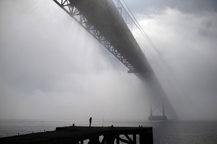 A fisherman smokes a cigarette as he waits near his rod under the April 25th Bridge by the Tagus riverbank during a foggy morning, in Lisbon on Tuesday. The bridge was named for the date the Carnations revolution restored democracy in Portugal in 1974. (Francisco Seco/AP)