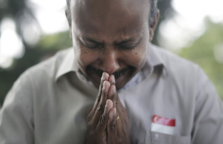 """Gunasegaran S., 51, from Singapore prays quietly outside the Istana presidential palace where boards were erected for members of the public to offer their condolences, Monday, March 23, 2015, in Singapore. Singaporeans wept and world leaders paid tribute Monday as the Southeast Asian city-state mourned the death of its founding father Lee Kuan Yew. The government announced that Lee """"passed away peacefully"""" several hours before dawn at Singapore General Hospital. He was 91. (AP Photo/Wong Maye-E)"""