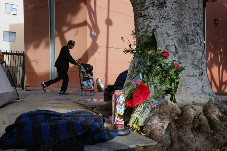 A pedestrian walks past flowers and candles placed on a sidewalk near where a man was shot and killed by police in the Skid Row section of downtown Los Angeles, Monday, March 2, 2015. Three Los Angeles police officers shot and killed the man on Sunday, as they wrestled with him on the ground, a confrontation captured on video that millions have viewed online. Authorities say the man was shot after grabbing for an officer's gun. (AP Photo/Richard Vogel)