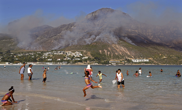 Children swim as the remainder of a fire burns at Hout Bay on the outskirts of the city of  Cape Town, South Africa, on Tuesday. (Schalk van Zuydam/AP)