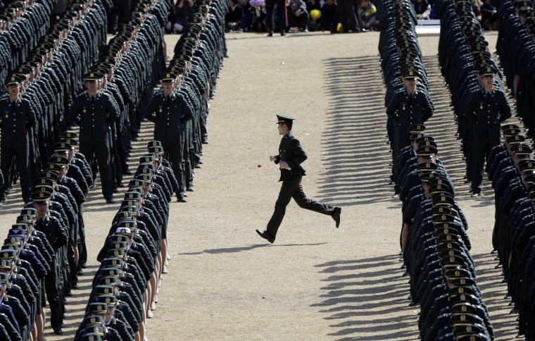 A South Korean military officer runs to his position during the joint commission ceremony of 6,478 new military officers of the army, navy, air force and marines at the military headquarters in Gyeryong, south of Seoul, South Korea, Thursday, March 12, 2015. (AP Photo/Lee Jin-man)
