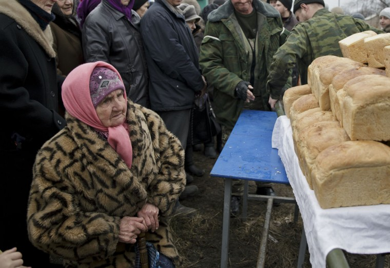 """An elderly woman looks as bread, baked by Russia-backed separatists, is brought to be delivered to residents in Chornukhyne, Ukraine, Monday, March 2, 2015. More than 6,000 people have died in eastern Ukraine since the start of the conflict almost a year ago that has led to a """"merciless devastation of civilian lives and infrastructure,"""" the U.N. human rights office said Monday. (AP Photo/Vadim Ghirda)"""